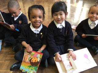 Smiling pupils with books St George's CE Primary