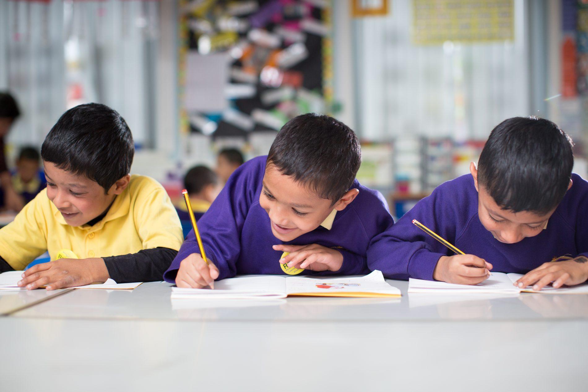 3 pupils writing Burnley Brow Community School