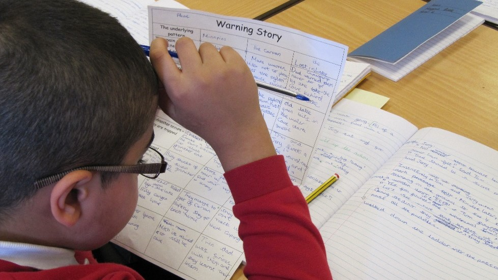 Pupil concentrating on writing Yew Tree Community School