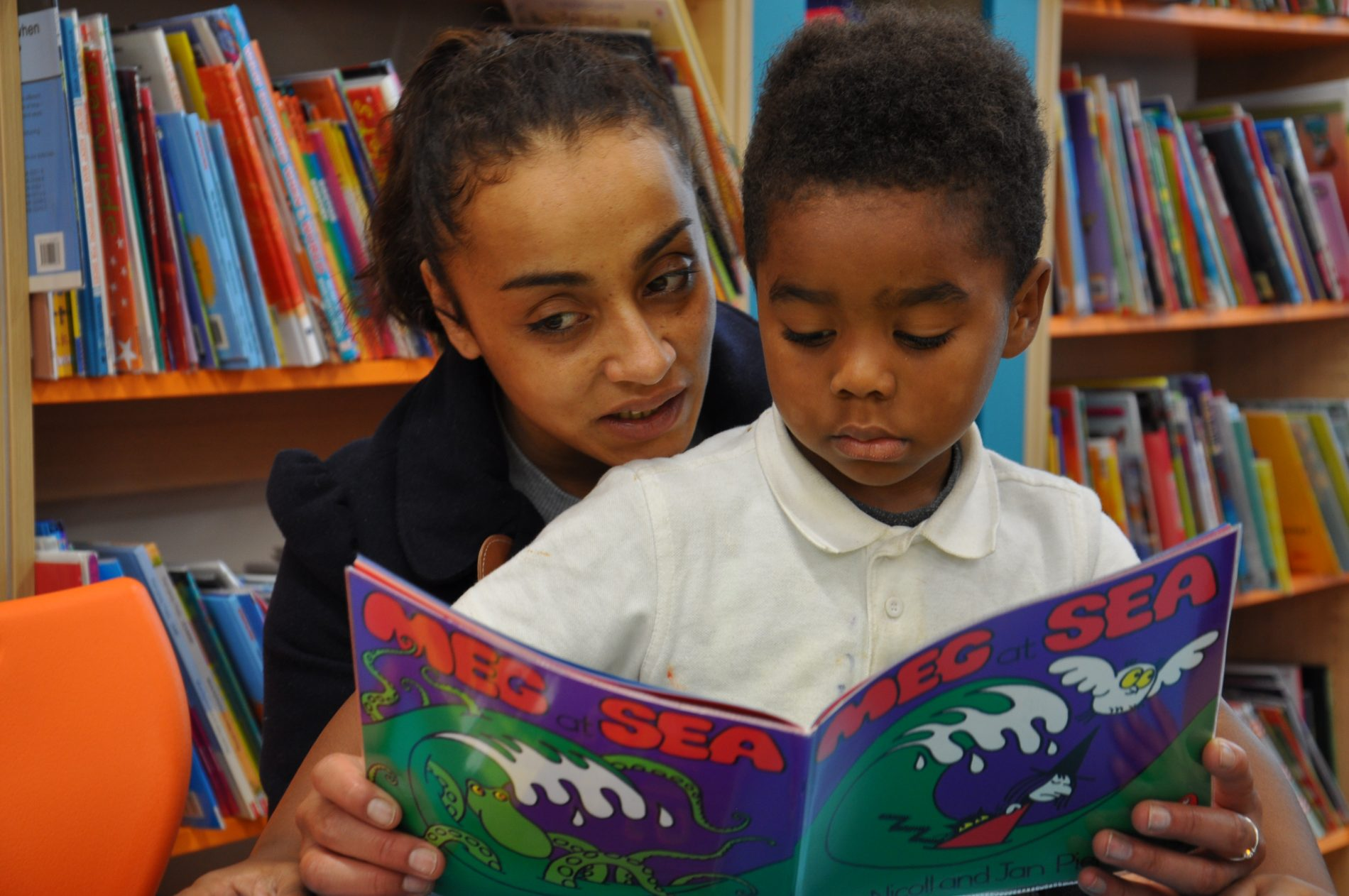 Teacher and pupil sharing reading book